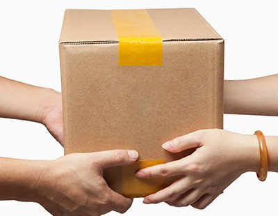 Someone handing a package to another to complete door to door services